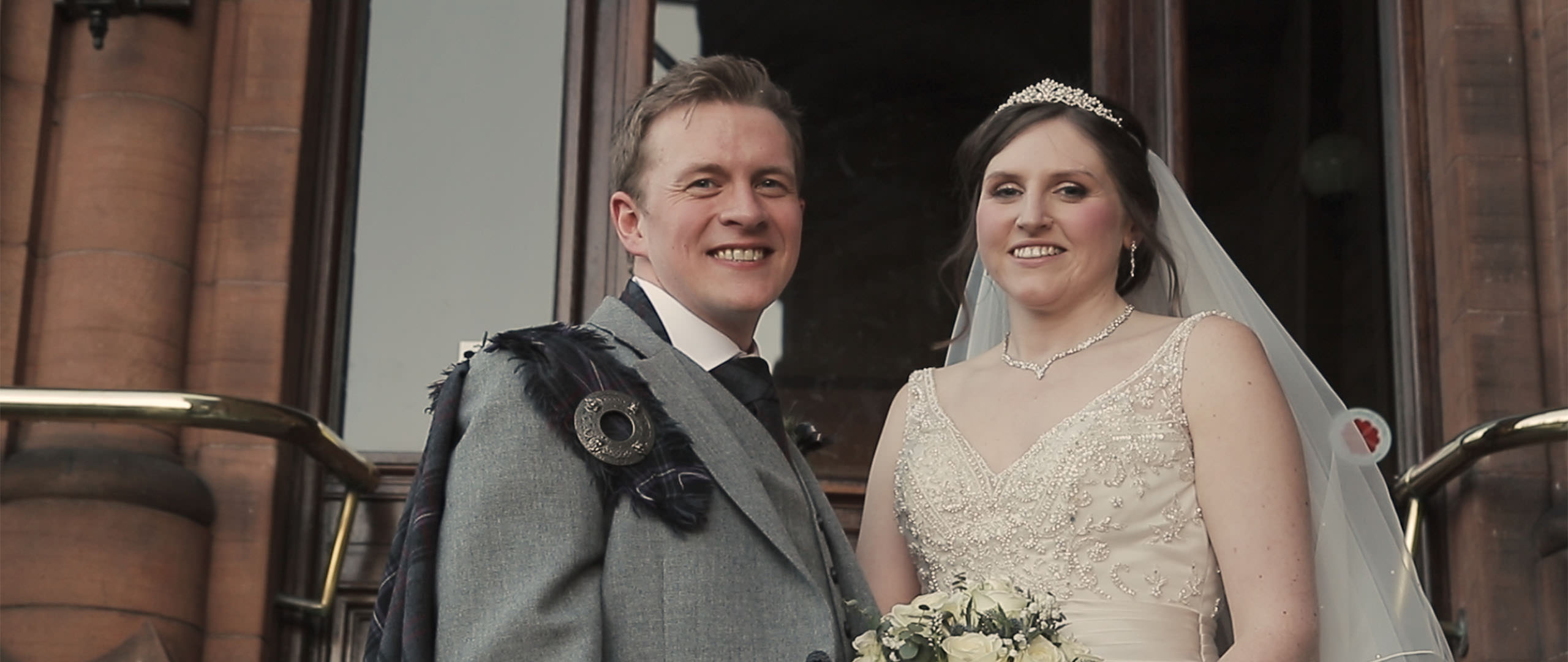 Wedding couple standing on the stairs to the Sherbrooke Castle Hotel in Glasgow